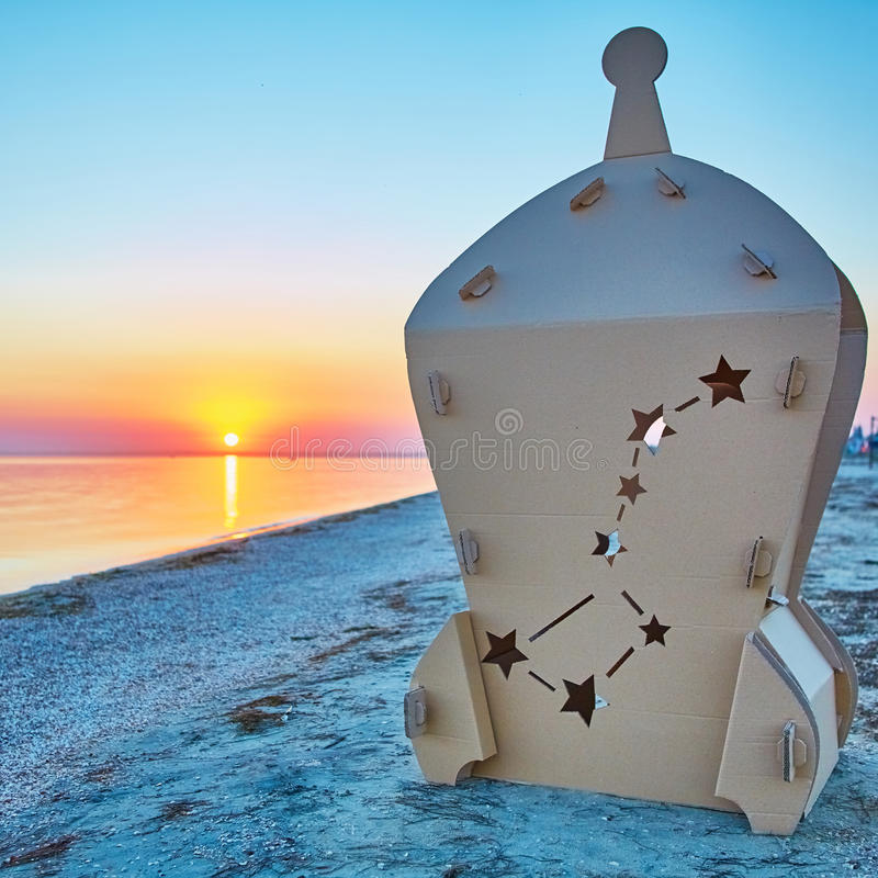 Cardboard toy spaceship at sea coast and sunset. Eco concept royalty free stock photo
