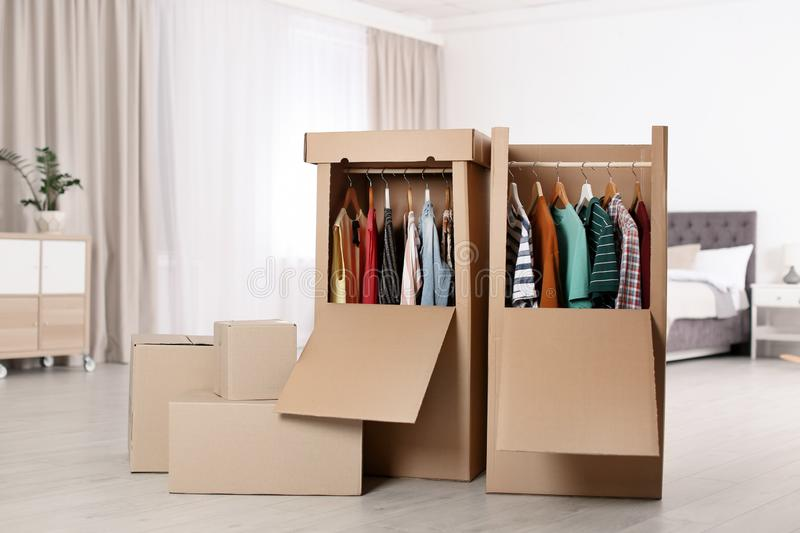 Cardboard wardrobe boxes with clothes on hangers in bedroom. royalty free stock photos
