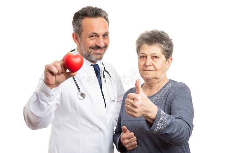Cardiólogo que muestra el corazón y el pulgar de la tenencia del paciente para arriba imagen de archivo