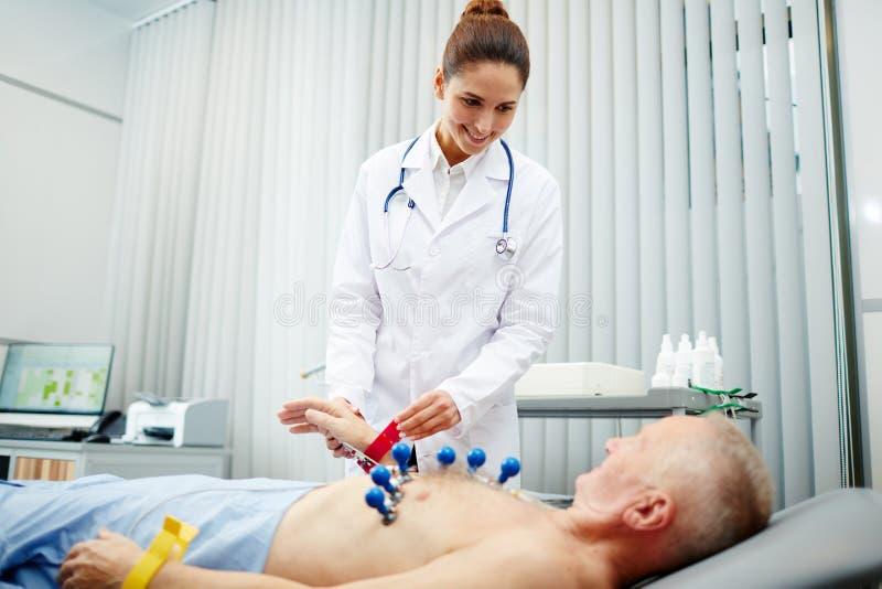 Cardiólogo sonriente que prepara al paciente para el procedimiento foto de archivo libre de regalías