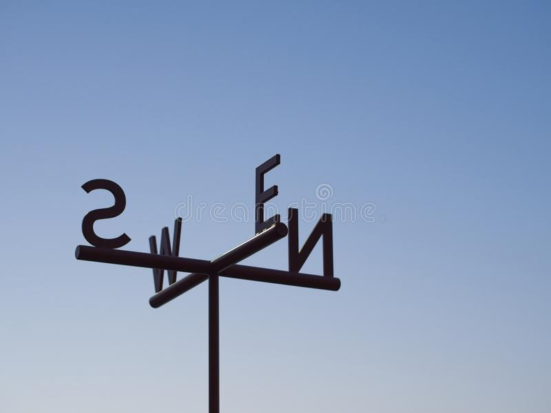 Cardinal Direction Direction pointer Sign against blue sky royalty free stock photography
