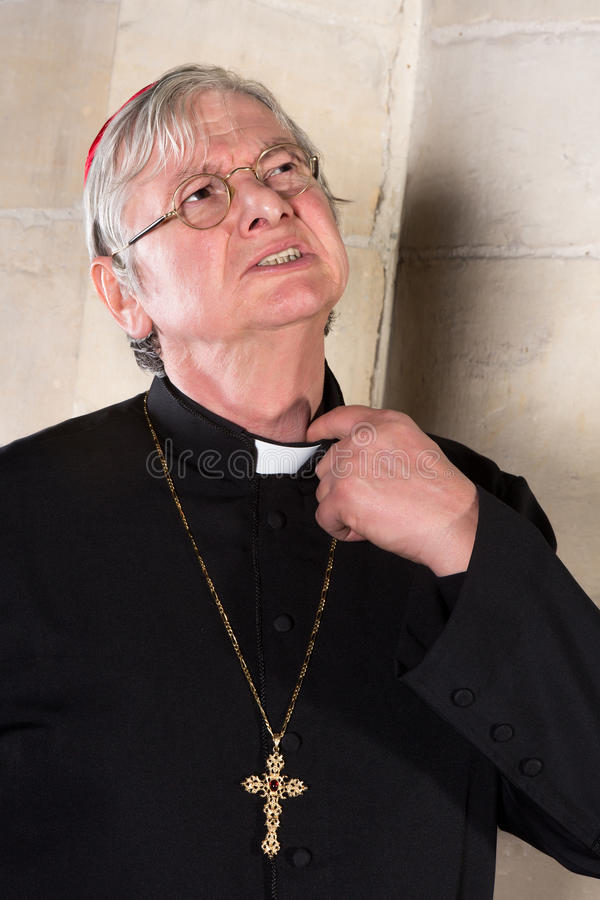 Cardinal with pinching collar. Mature cardinal annoyed by the pinching priest collar in his shirt or cassock royalty free stock photos