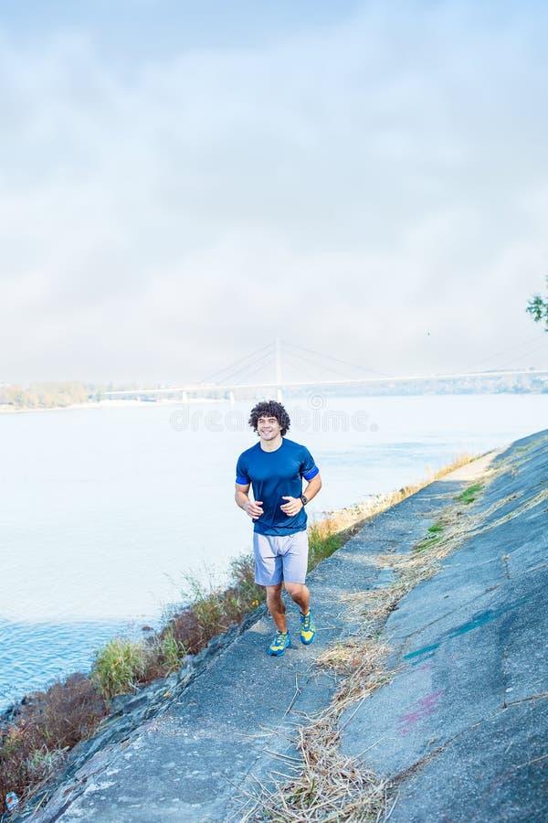 Cardio övning - man som utomhus joggar och kör i natur royaltyfri bild