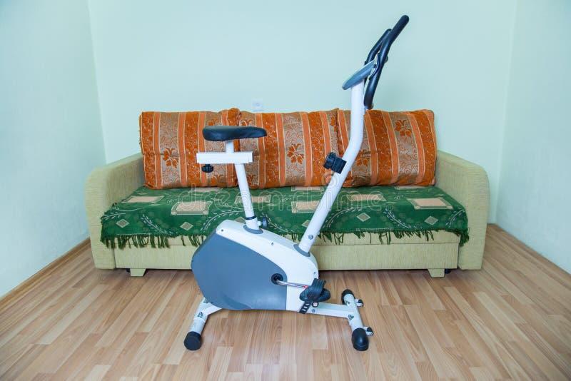 Cardio bici bianca di forma fisica Sofà e salone r immagine stock