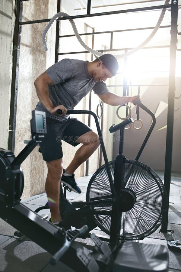 cardio genomkörare Sportmanutbildning på cykeln som cyklar övning arkivfoto