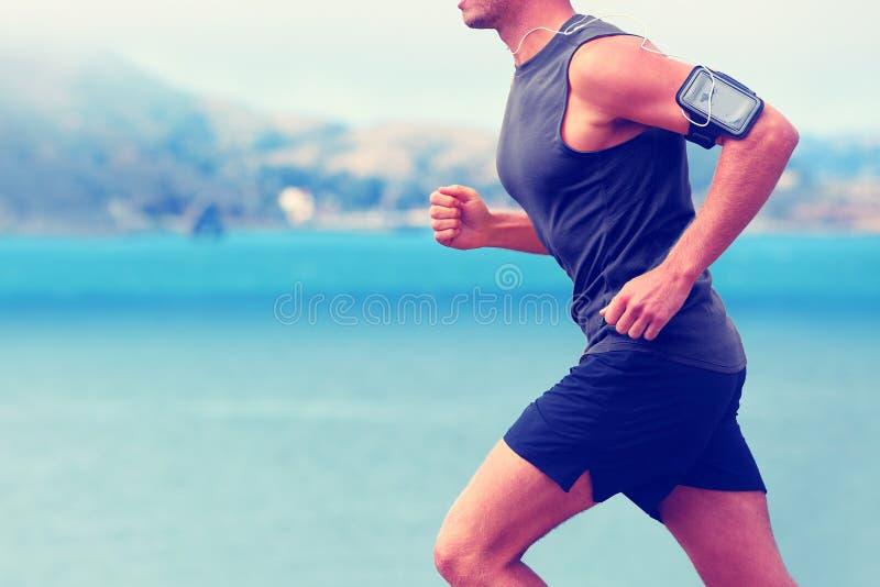 Cardio runner running listening smartphone music stock photography