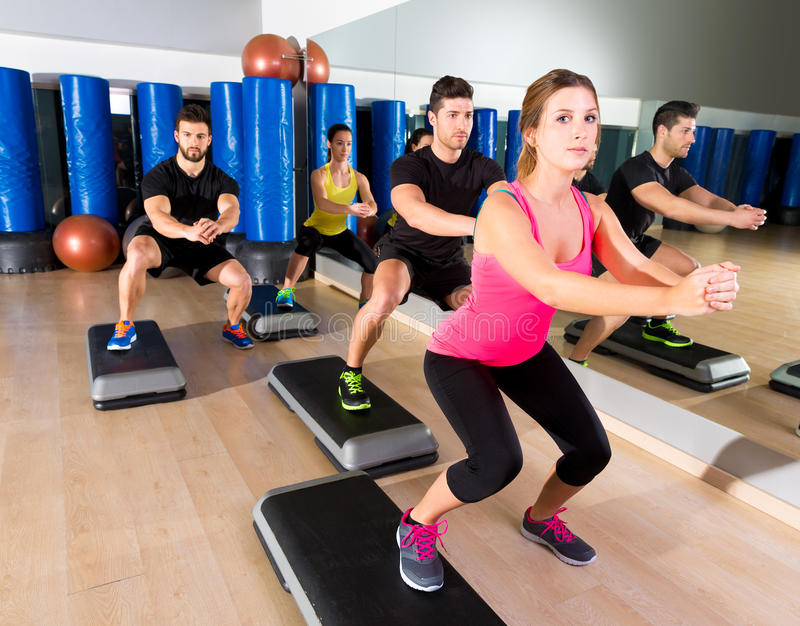 Cardio step dance squat group at fitness gym. Cardio step dance squat people group at fitness gym training workout royalty free stock photo