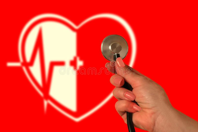 Cardio therapy concept. Hand with stethoscope on red background. Blurred image of heart, medical cross and electrocardiogram. Hospital treatment or clinic stock photography