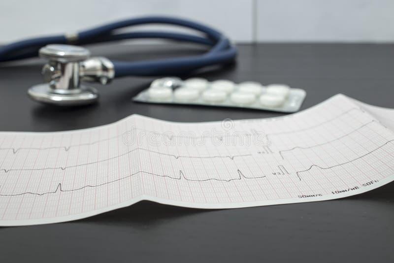 Cardiogram, голубой стетоскоп и таблетки лежат на темной таблице в офисе доктора, на фоне белой стены стоковые фотографии rf