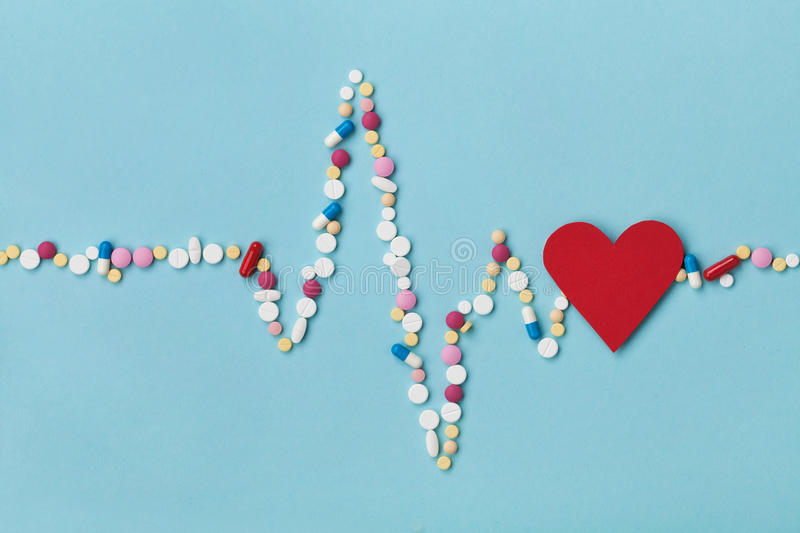 Cardiogram is made of colorful drug pills and red paper heart, pharmaceutical and cardiology concept royalty free stock images