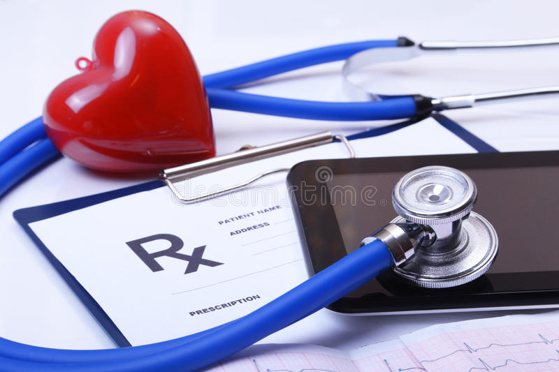 Cardiogram with stethoscope and red heart on table, closeup.  stock images