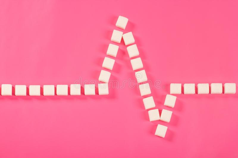 Cardiogram of sugar cubes on pink background stock image