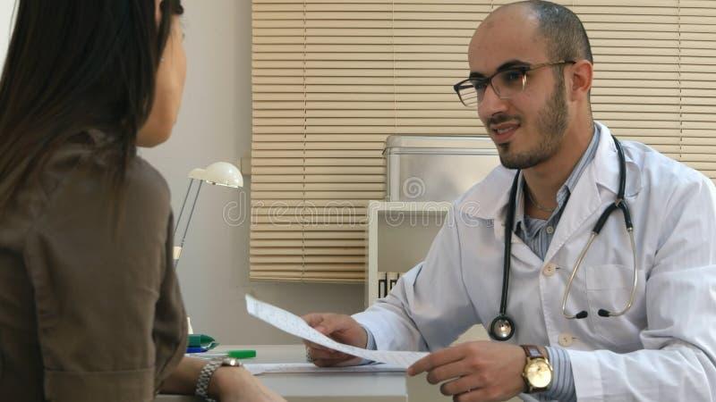 Cardiograma de explicación del doctor de sexo masculino árabe al paciente femenino foto de archivo