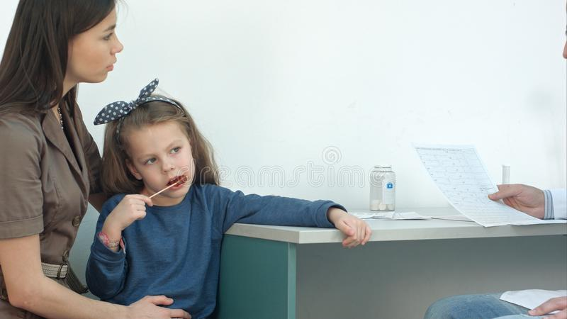 Cardiogramme de explication de docteur masculin à la mère sérieuse avec la petite fille sur elle recouvrements photos stock