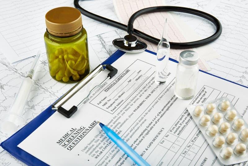 Cardiogrammen, stethoscoop, medische vragenlijst en fles met pillen stock afbeeldingen