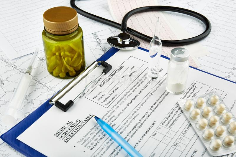 Cardiograms, stethoscope, medical questionnaire and bottle with pills. stock images