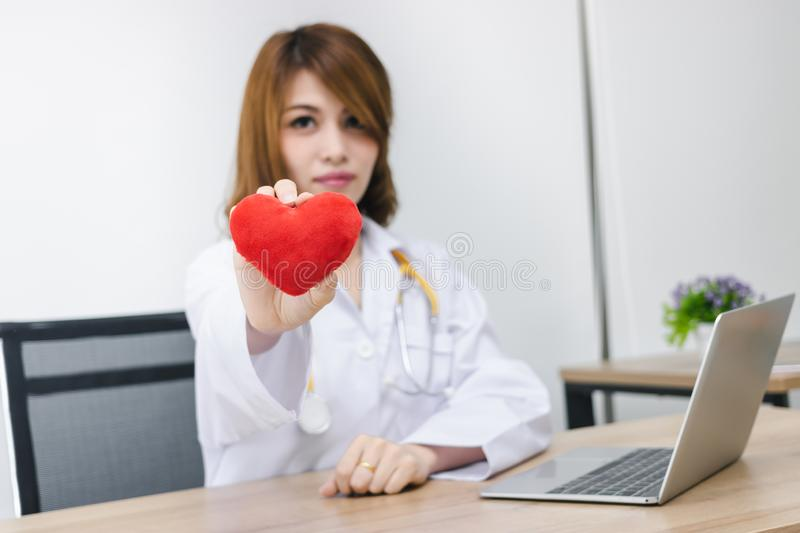Cardiologist Asian female doctor with red heart in hands. Healthy care and medical concept. Selective focus and shallow depth of. Field stock photography
