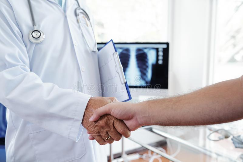 Handshake of doctor and patient. Cardiologist shaking hand of male patient in clinic stock photos