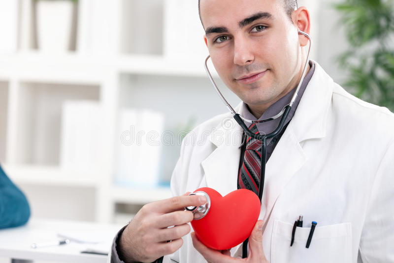 Cardiologist. Young cardiologist holding red heart and stethoscope royalty free stock image