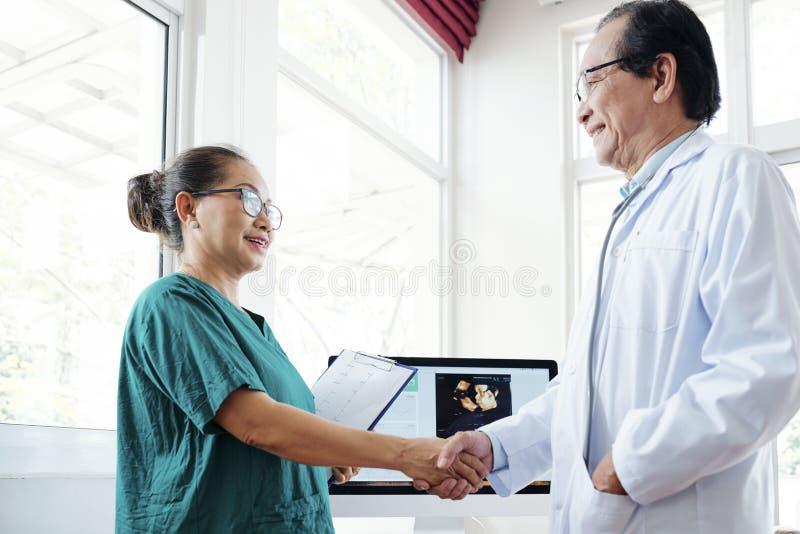 Cardioloog en chirurgen het schudden handen stock foto