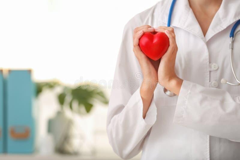 Cardioloog met rood hart in kliniek stock afbeelding