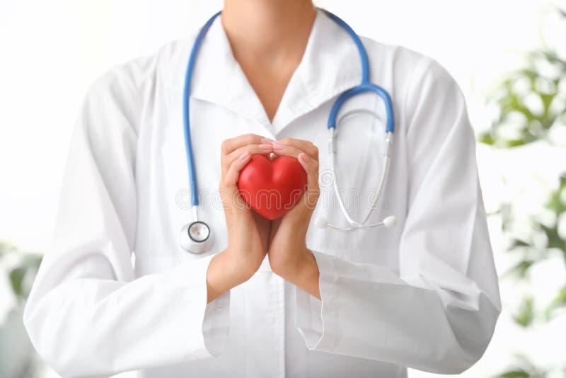 Cardioloog met rood hart in kliniek stock afbeeldingen