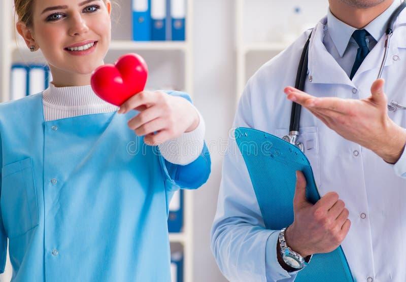 Cardioloog met zijn verpleegster het hulp stellen in het ziekenhuis royalty-vrije stock afbeeldingen