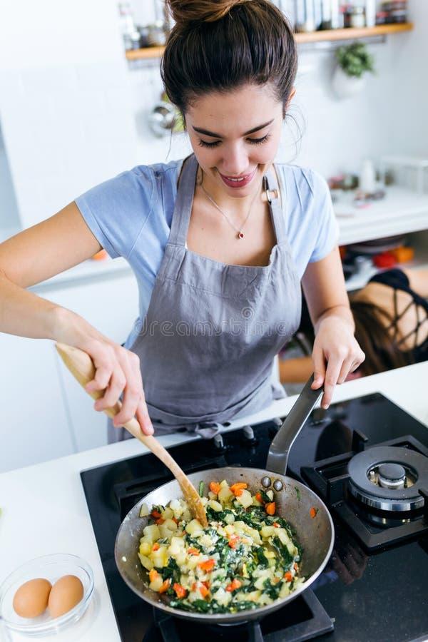 Cardons de mélange de jeune femme, pommes de terre, poivron rouge et oeufs dans la casserole image libre de droits
