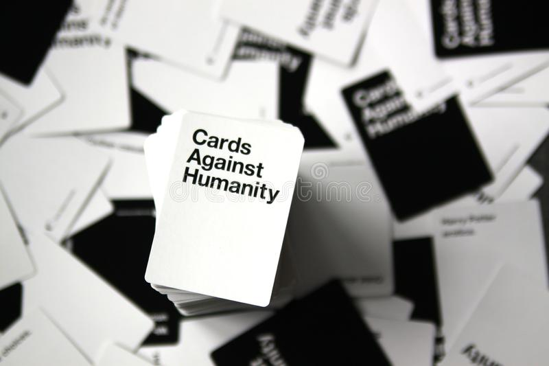 Cards Against Humanity overhead view with scattered cards in background stock photo