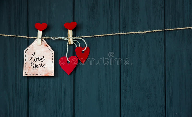 Cards with Desires Love Valentine`s card `Love You` natural cord and red pins hanging on rustic black texture background, Copy Spa royalty free stock images