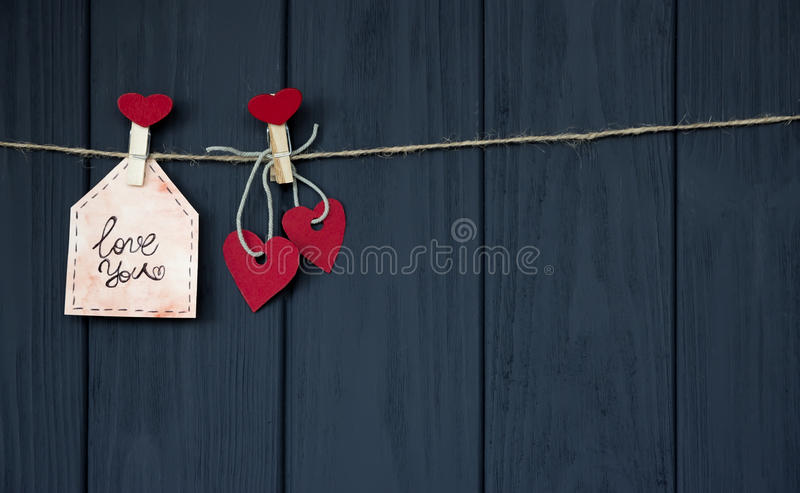 Cards with Desires Love Valentine`s Hearts natural cord and red pins hanging on rustic texture background, Copy Space. royalty free stock image