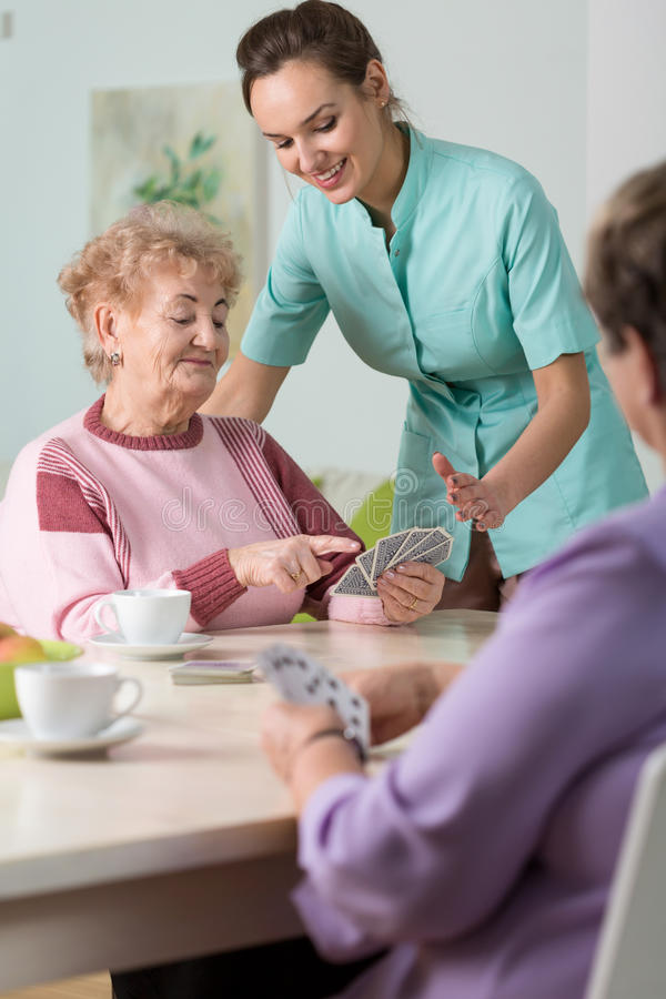 Cards in nursing house. Nurse playing cards with elderly women royalty free stock image