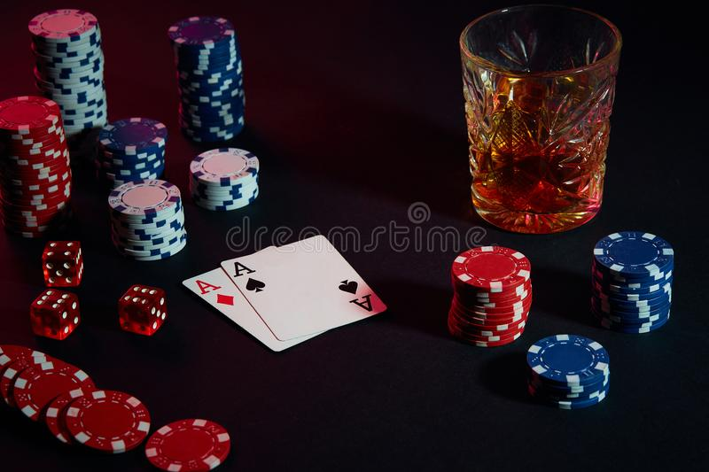Cards of poker player. On the table are chips and a glass of cocktail with whiskey. Combination of cards stock photography