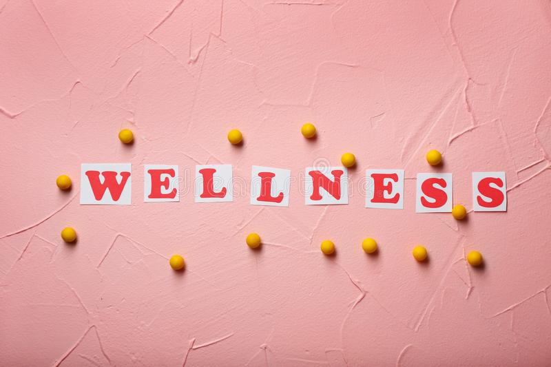 Cards with word WELLNESS and pills on color background. Health care concept stock photography