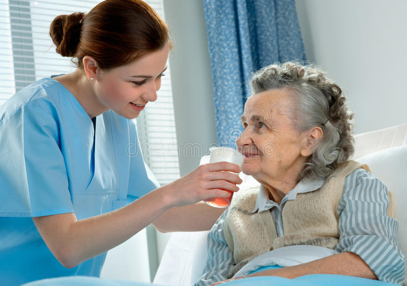 Care. Nurse cares for a elderly woman lying in bed