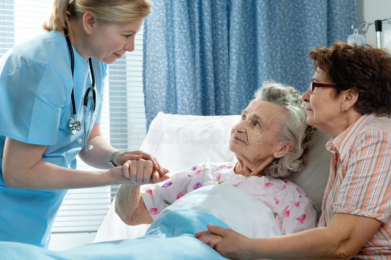 Care. Doctor talking to elderly patient lying in bed in hospital