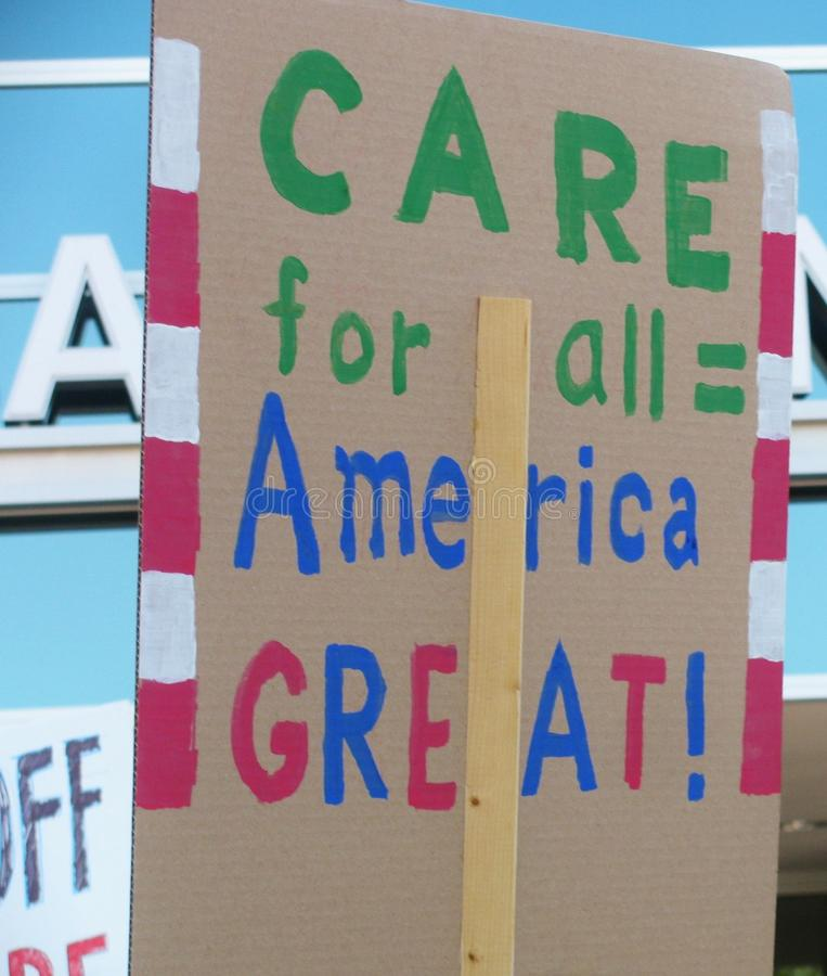 Care for all equals America great sign at Los Angeles area healthcare rally. TORRANCE, CALIFORNIA - JULY 3, 2017: Sign at a rally to stop Republican Trumpcare stock image