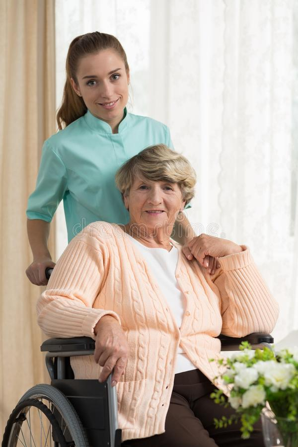 Care assistant pushing the wheelchair royalty free stock photo