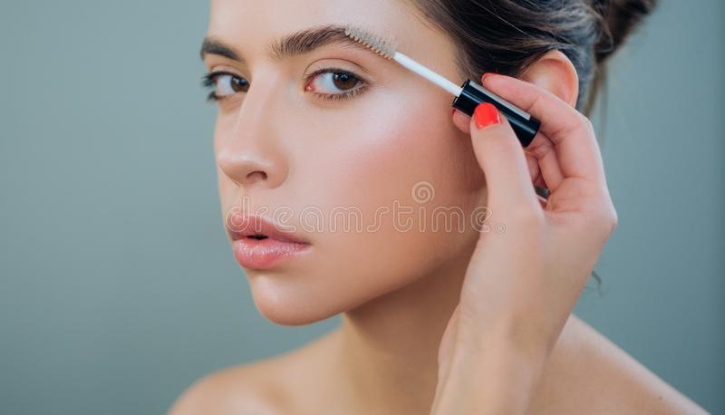 Care beauty eyebrow. Beautiful woman with brow brush in hand. Attractive sexy girl with glamorous professional nude royalty free stock image