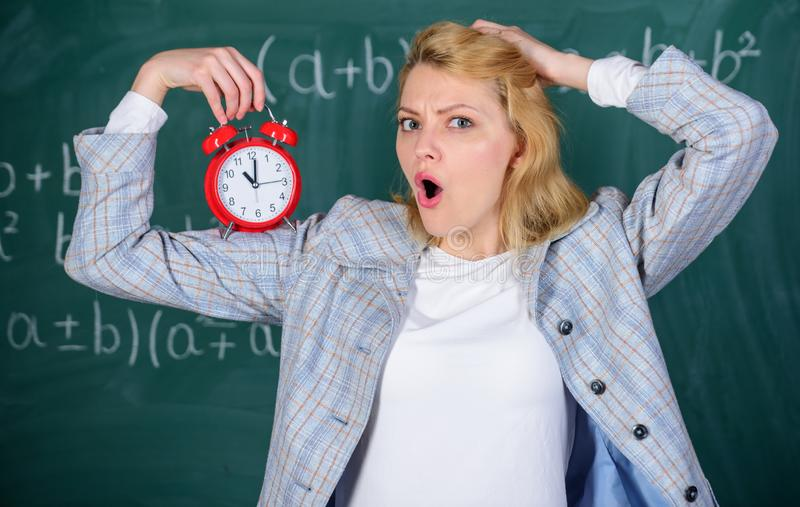 She care about discipline. Woman teacher hold alarm clock. Lessons schedule concept. Time for break. Girl wonder about. Time. Welcome teacher school year stock images