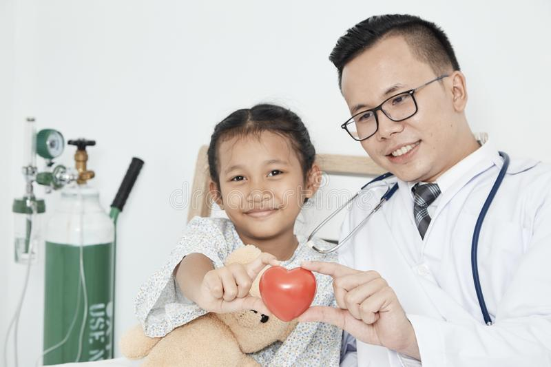 Young male doctor pediatrician checking girl stock image