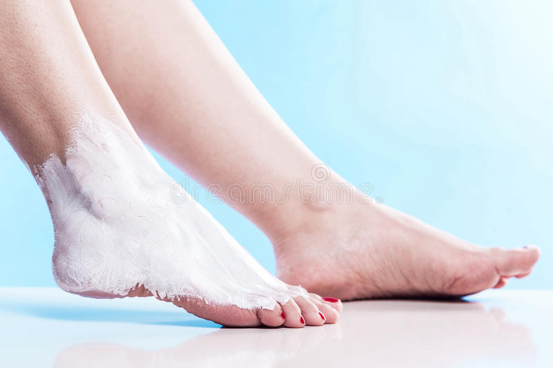 Care for dry skin on the well-groomed feet and heels with creams. For the skin and feet royalty free stock image
