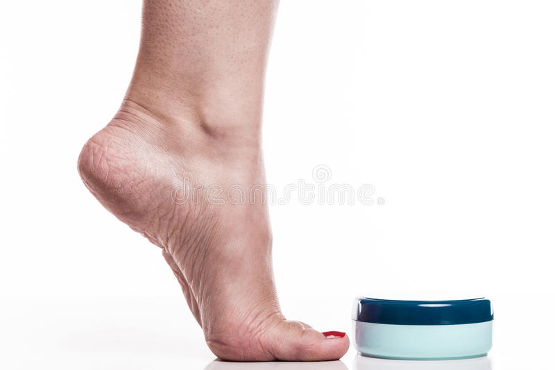 Care for dry skin on the well-groomed feet and heels with creams. For the skin and feet royalty free stock photography