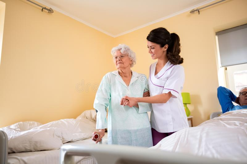 Care of the elderly at nursing home. Nurse helps to senior women to walk with crutches royalty free stock image