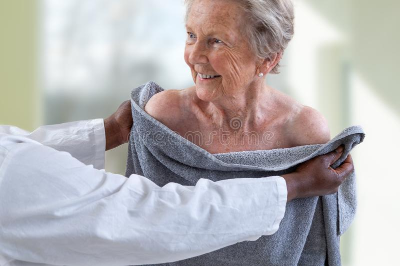 Care giver or nurse assisting elderly woman for showerand drying her. Care giver or nurse assisting elderly woman for shower stock images
