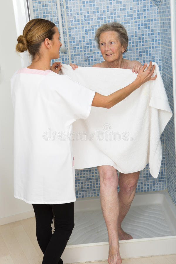 Care giver or nurse assisting elderly woman for shower. Care giver or nurse assisting elderly women for shower at home or retirement house royalty free stock photo