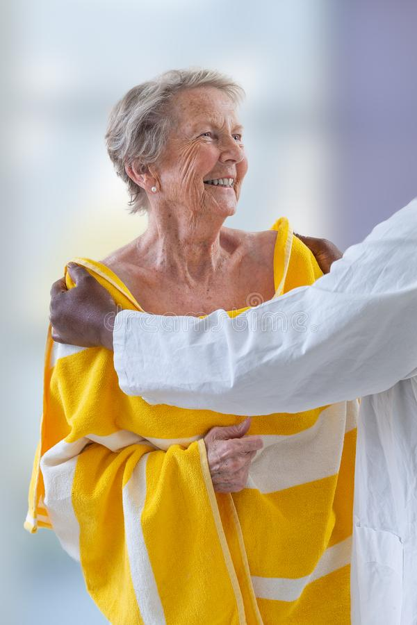 Care giver or nurse assisting elderly woman for showerand drying her. Care giver or nurse assisting elderly woman for shower royalty free stock images