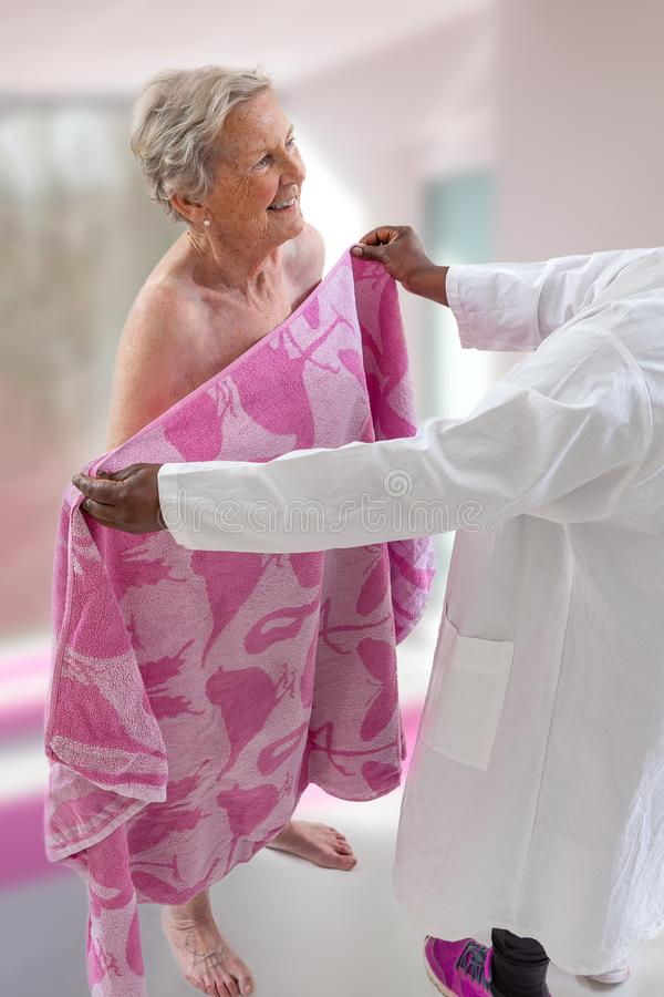 Care giver or nurse assisting elderly woman for showerand drying her. Care giver or nurse assisting elderly women for shower stock photography