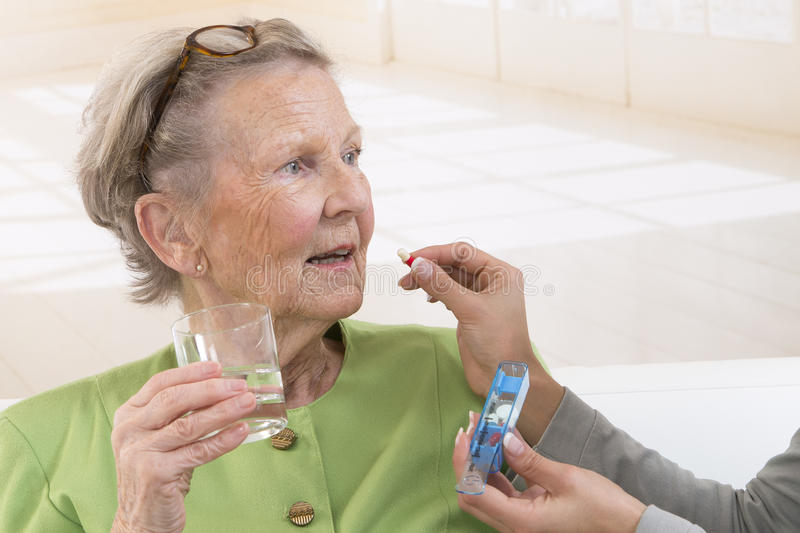 Care giver or nurse giving to elderly woman her pills. Care giver or nurse giving to elderly women medicine stock image