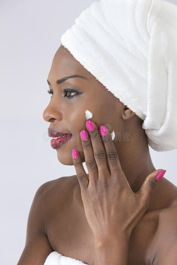 care henne att ta för hud Stående av den härliga unga Afro--amerikan kvinnan som slås in i fördelande kräm för handduk på hennes  royaltyfria bilder
